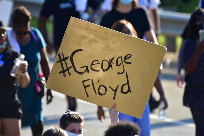 A protester holding up a yellow board that says George Floyd