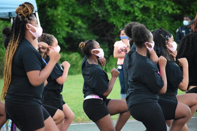 Black girls in Black T shirts and shorts wearing pink masks dancing