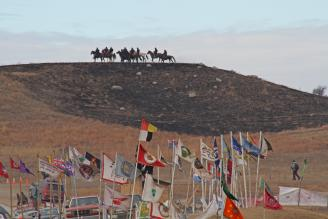 Riders on horseback overlook Oceti Sakowin Camp occupied by Standing Rock protesters.