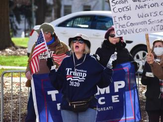 A White woman with blond hair, wearing a hat. She has a Trump 2020 sweatshirt on, and is holding an Amerian Flag and a water bottle. Her mouth is open like she's shouting something.