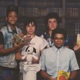 Young Eric Ward posing with friends holding books