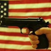 A hand gripping a handgun in front of an American flag backdrop