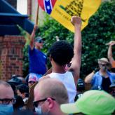Pro-confederacy protestor holds up a confederate flag, a counter-protestor raises a fist in response.