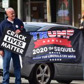 "Two men holding a flag that says Trump 2020 The Sequel and banners saying ""crack lives matter"""