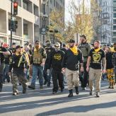 A group of men, in Proud Boys gear walking on a street.