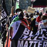 Protesters holding a black lives matter flag and walking