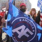 "A man holding an ""America First"" flag, wearing a red MAGA hat, and a black face mask in a crowd of other right-wingers."
