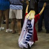 A white woman with blond hair, kneeling with her arms in the air, a Trump flag tied around her neck and hanging down her back