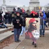 A woman wearing a red hat, holding a paining of Jesus wearing a Make America Great Again hat.