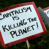 "A red and white sign that says ""capitalism is killing the planet!"""