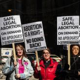 "Three women at a prochoice rally holding signs that say ""Safe, legal abortion on demand. No apologies!"" and ""Abortion is a right. No Going Back."""