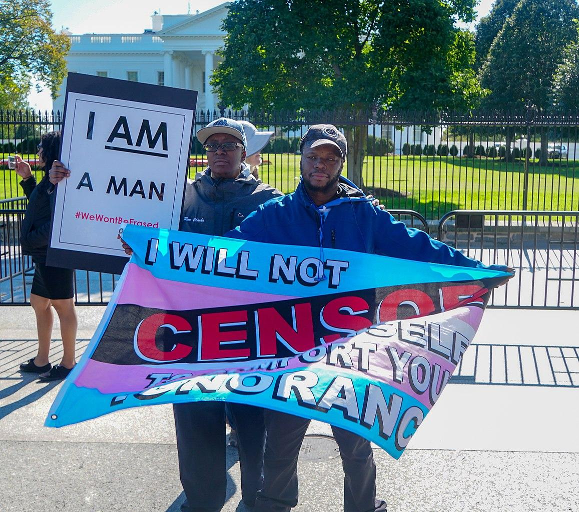 Two protesters hold signs at a rally for trans rights