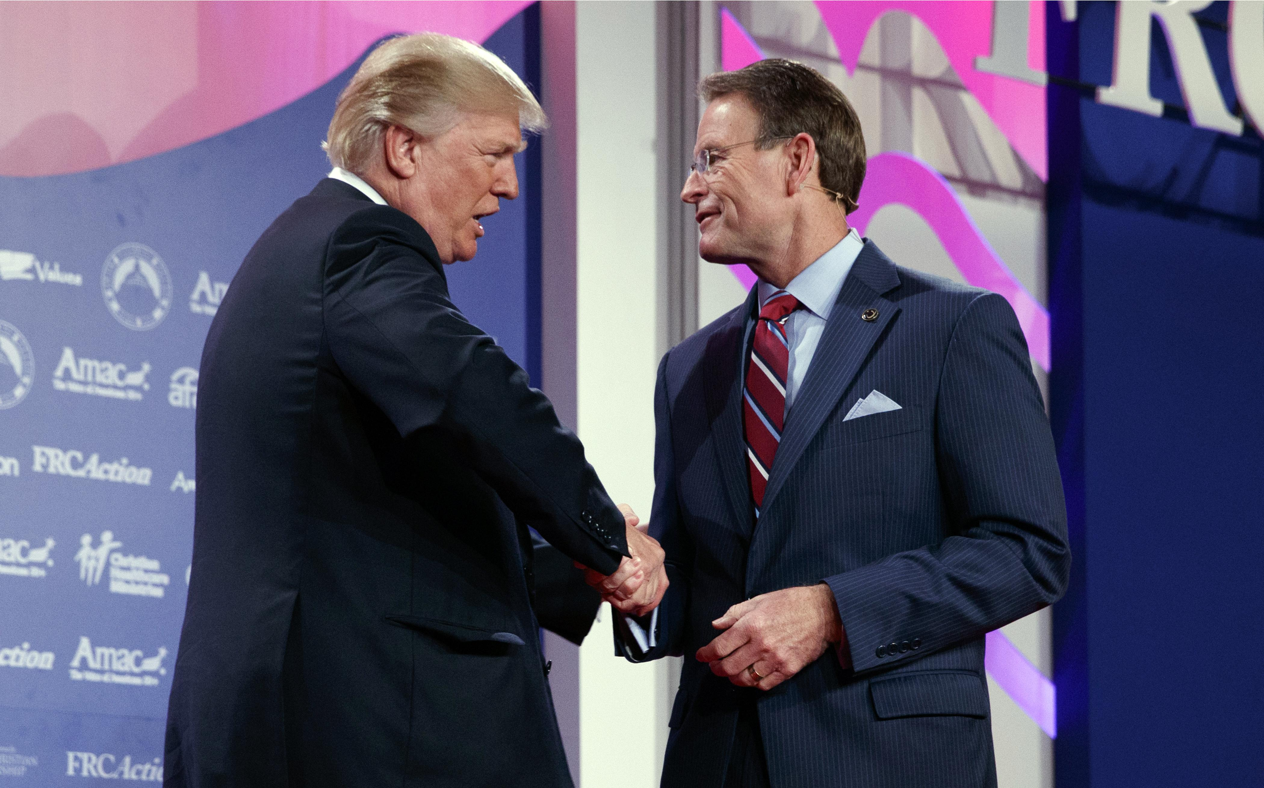 Donald Trump shakes hands with Family Research Council president Tony Perkins at the 2017 Value Voters Summit, Friday, Oct. 13, 2017, in Washington.