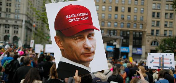 Protest sign of Putin wearing MAGA hat