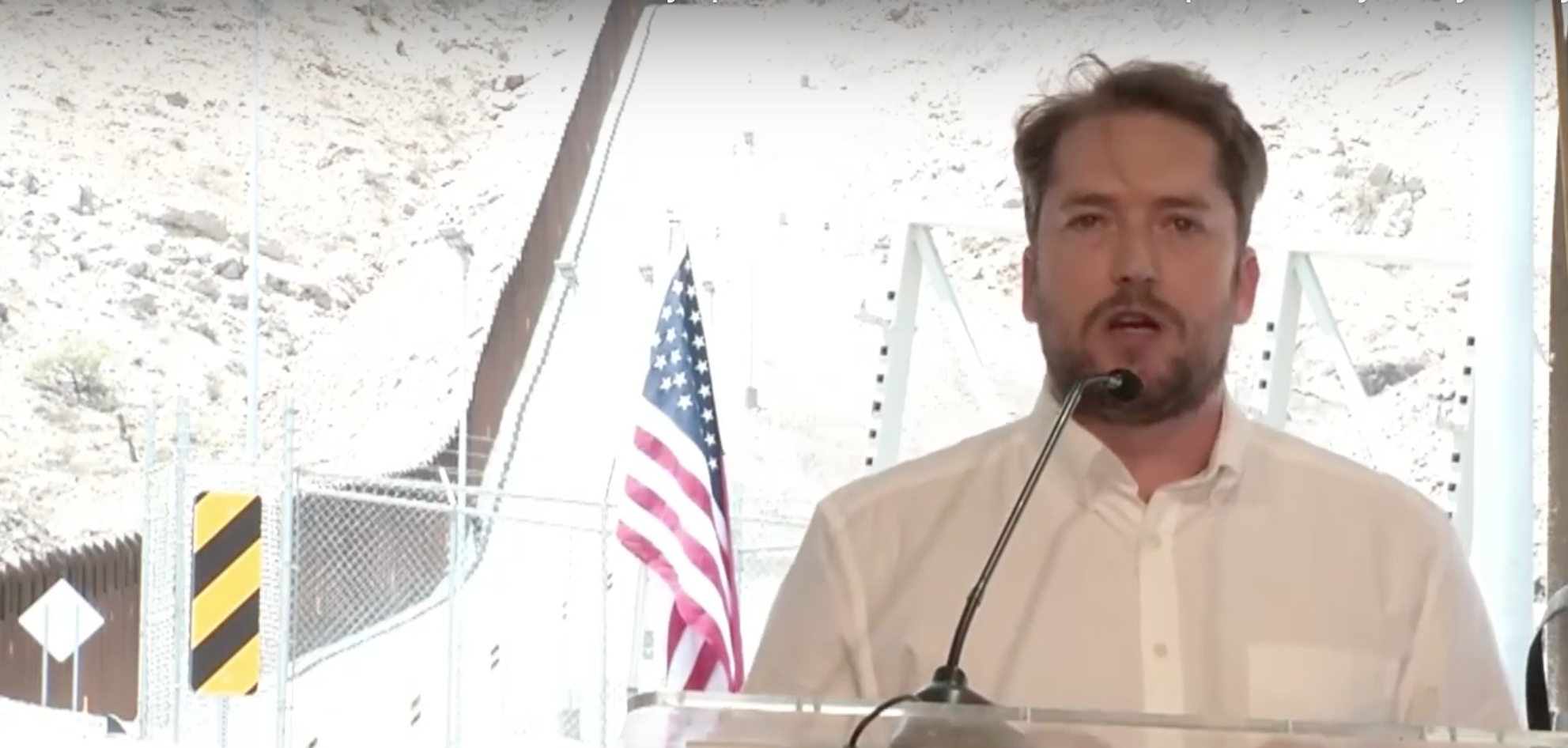 Darren Beattie delivers speech in NM with U.S.-Mexico border wall construction behind him.