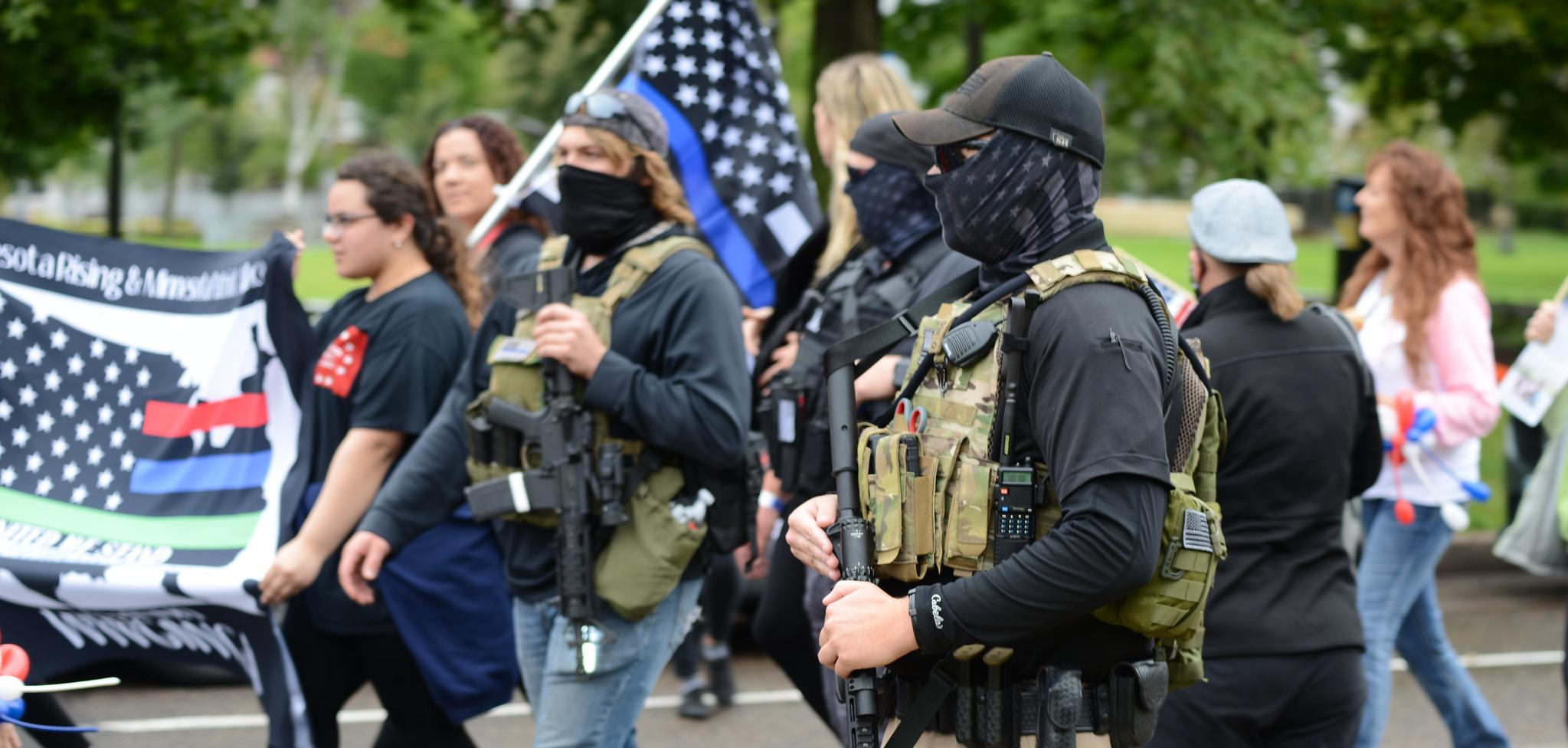 Armed militia members march next to a WWG1WGA flag, a common identifier of QAnon believers, at the United We Stand & Patriots March for America, St. Paul, Minnesota, September 12, 2020 (Credit: Fibonacci Blue/Flickr).