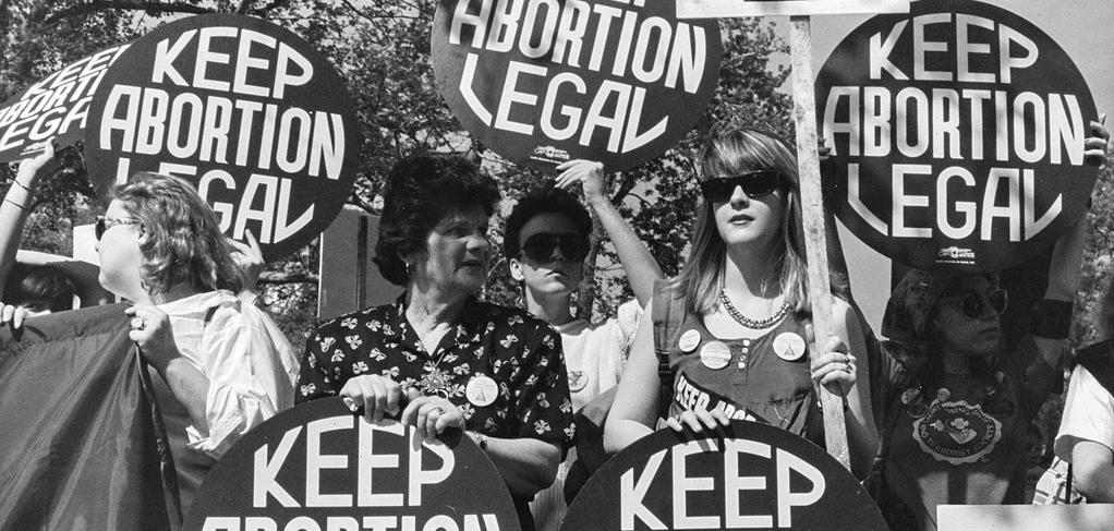 "White women protesting, holding circular signs that say ""Keep Abortion Legal"""
