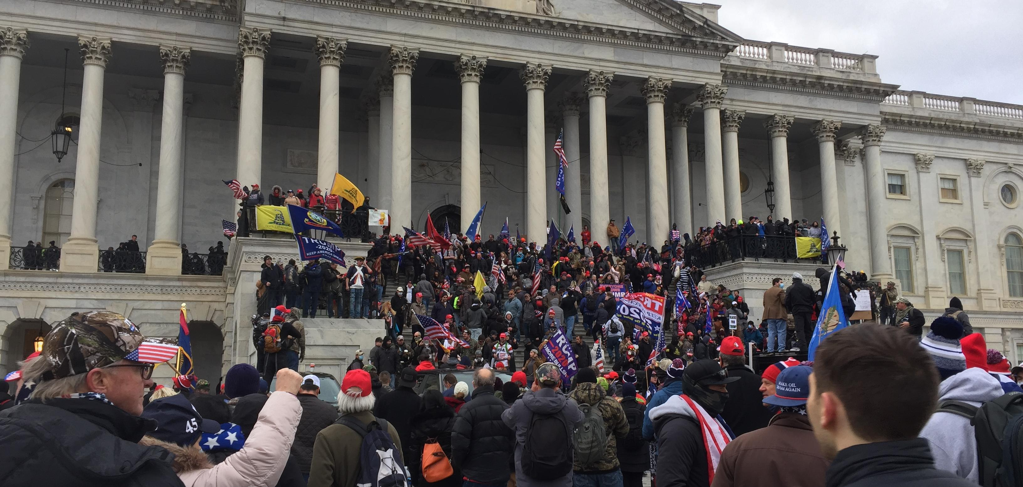 A group of right wing protesters outside the Capitol building in Washington DC. They are climbing the Stairs of the building.